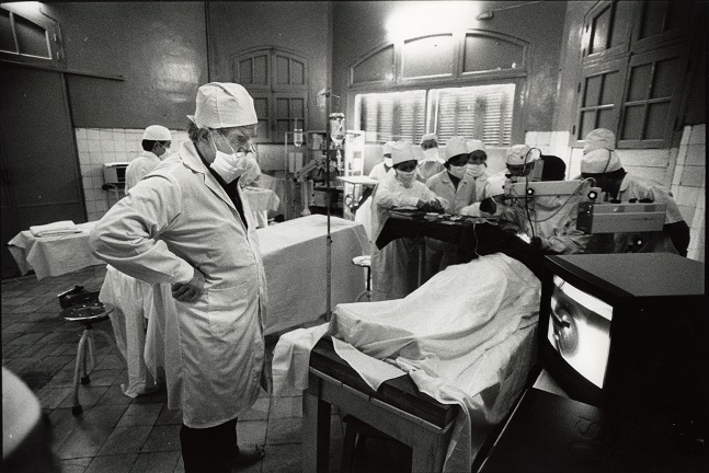 Professor Fred Hollows watches the video screen donated to the Institute of Ophthalmology as Vietnamese eye surgeons watch Dr Sanduk Ruit perform cataract extraction in Hanoi, Vietnam in 1992. Photo: Michael Amendolia