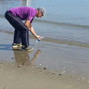 Collecting sample of Atlanic Oceean prior to coast-to-coast walk
